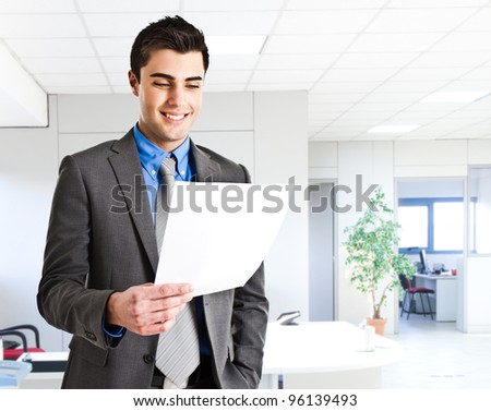 Smiling businessman reading a document