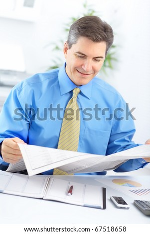 Smiling businessman reading a newspaper in the office