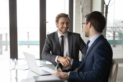 Smiling businessman shaking client hand, closing successful deal, sitting at table with laptop in office, satisfied hr manager hiring new employee, business partners handshaking at meeting
