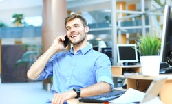 Smiling businessman sitting and using mobile phone in office.