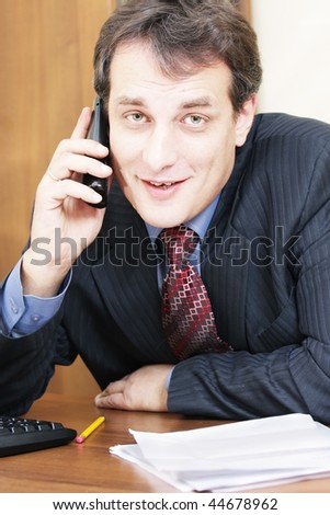 Smiling businessman sitting at desk with black cordless phone