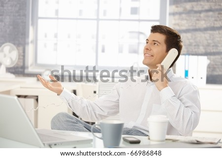 Smiling businessman sitting at office desk on landline phone call, looking up, raising hand.?