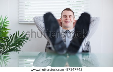 Smiling businessman sitting back behind a table