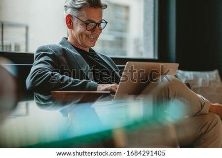 Smiling businessman sitting in office lobby working on laptop. Male business professional working in office lobby.