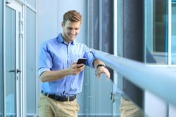 Smiling businessman standing and using mobile phone in office.