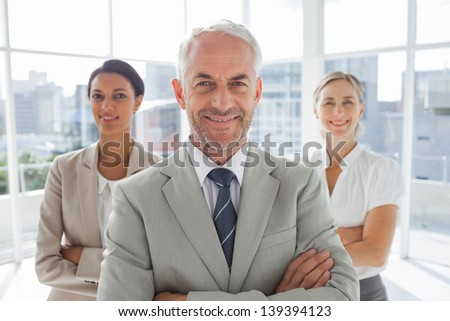 Smiling businessman standing in front of colleagues with arms folded