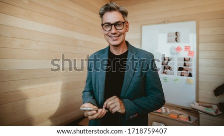 Smiling businessman standing in meeting room. Business professional in formalwear wearing eyeglasses with a smart phone in hand looking at camera.
