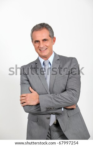 Smiling businessman standing on white background - stock photo