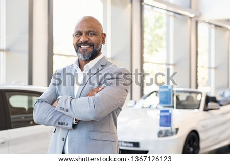 Smiling businessman standing with arms crossed at new car showroom. Confident senior car dealer in dealership while looking at camera. Portrait of professional black salesman in luxury auto showroom. #1367126123