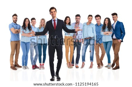 smiling businessman team leader welcomes you with both hands in his casual team while standing on white background. He is wearing a black suit and they are wearing blue shirts and jeans, full body #1125194165