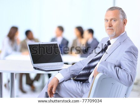 Smiling businessman using a laptop with his team in the background