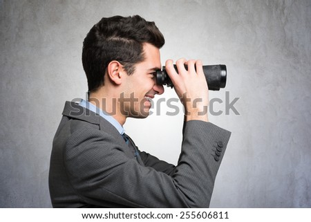 Smiling businessman using binoculars #255606811