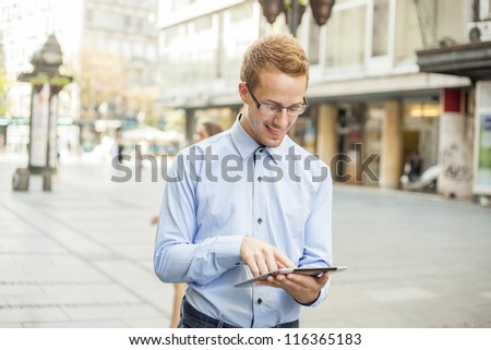 Smiling Businessman Using Tablet Computer on street in public space