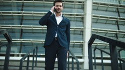 Smiling businessman walking downstairs in stylish suit at street. Confident business man talking smartphone near stadium. Cheerful man using mobile phone outdoors.