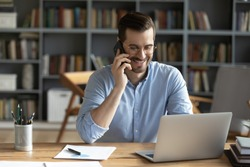 Smiling businessman wearing glasses talking on phone, sitting at desk with laptop, friendly manager consulting customer by phone, happy man chatting with friends distracted from work