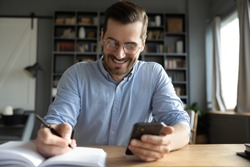 Smiling businessman wearing glasses using phone, writing important information in notebook, sitting at desk, happy man holding smartphone, making notes in personal daily planner, planning work day