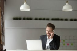 Smiling businessman wearing suit sitting at working desk using typing on laptop, making answering call, talking on the phone, consulting client about email by cell, holding mobile interview in office