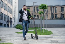 Smiling businessman with electric scooter standing near modern business building talking on phone.