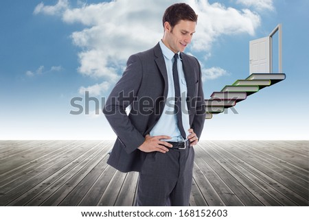 Smiling businessman with hands on hips against book steps leading to door against sky