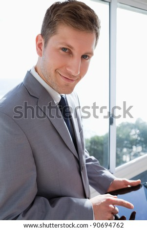 Smiling businessman with his tablet in front of the window