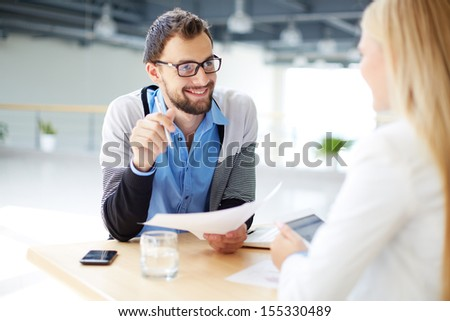 Smiling businessman with paper talking to his colleague at meeting