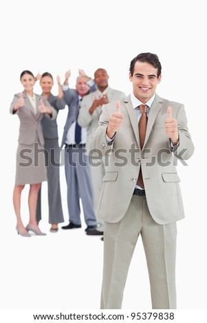 Smiling businessman with team behind him giving thumbs up against a white background