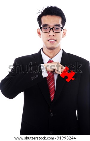 Smiling businessman with the missing piece of a puzzle