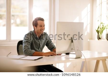 Smiling businessman working on computer. Man sitting at his work table working on computer at home listening to audio using earphones.