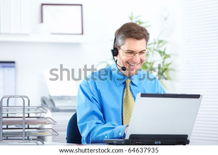 Smiling  businessman working with laptop and headset