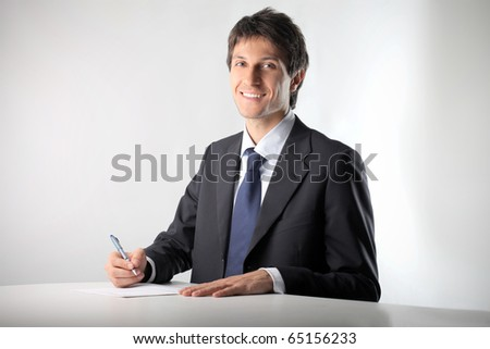 Smiling businessman writing a document