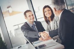 Smiling businessmen shaking hands after closing a deal.