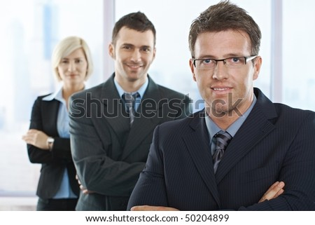 Smiling businesspeople looking at camera standing in a row with arms folded.