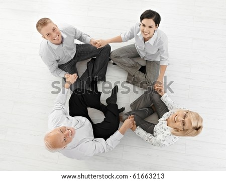 Smiling businessteam doing relaxation, looking at camera sitting on floor in lotus posture, high angle view.?