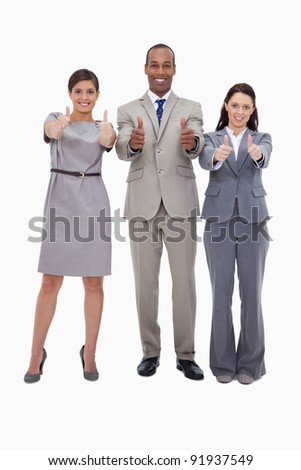 Smiling businessteam giving thumbs up against a white background