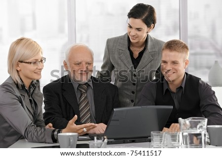 Smiling businessteam on meeting, mid-adult businesswoman showing computer work to coworkers.?
