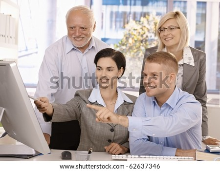 Smiling businessteam working together in office, looking at computer screen, pointing.?