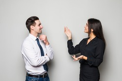 Smiling businesswoman and businessman are conversing against grey