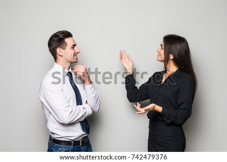 Smiling businesswoman and businessman are conversing against grey #742479376