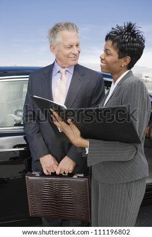 Smiling businesswoman and businessman with folder