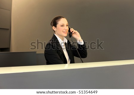 smiling businesswoman at the reception desk at the telephone