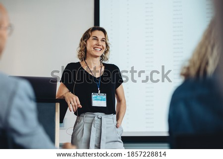 Smiling businesswoman delivering a speech during a conference. Successful business professional giving presentation.