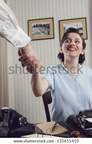 Smiling businesswoman doing an agreement, focus on hands