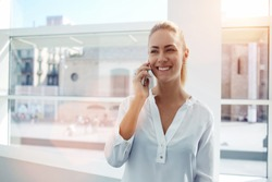 Smiling businesswoman dressed in formal wear having pleasant conversation on mobile phone with friend, happy attractive female speaking on cell telephone while resting in  office interior after work