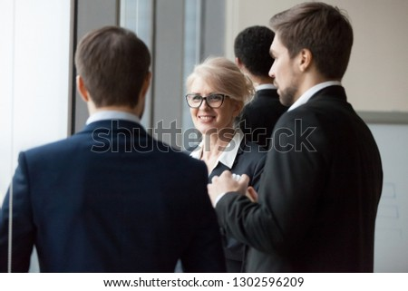 Smiling businesswoman enjoying friendly talk with male colleagues or partners, workers group having conversation communicating at break, executive board team chatting discussing work standing office