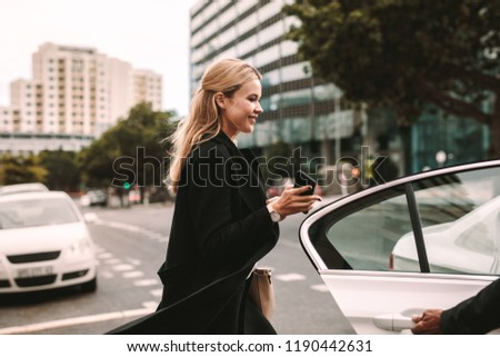 Smiling businesswoman getting into a taxi. Female commuter entering a taxi with driver opening door.