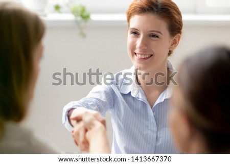 Smiling businesswoman greeting shaking hand female client, new colleague, vacancy candidate at meeting in office. Hiring sale bank investment deal start of negotiations job seeker applicant interview