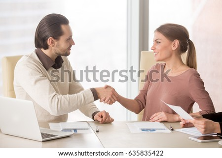 Smiling businesswoman handshaking with young male colleague, introducing herself before office meeting discussion, starting teamwork on project, new members of team shaking hands getting acquainted