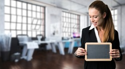 smiling businesswoman holding an empty blackboard in front of an office background