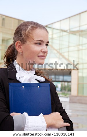 Smiling businesswoman holding clipboard near office building