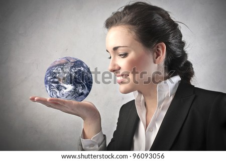"Smiling businesswoman holding the Earth in her hand ""Elements of this image furnished by NASA"""